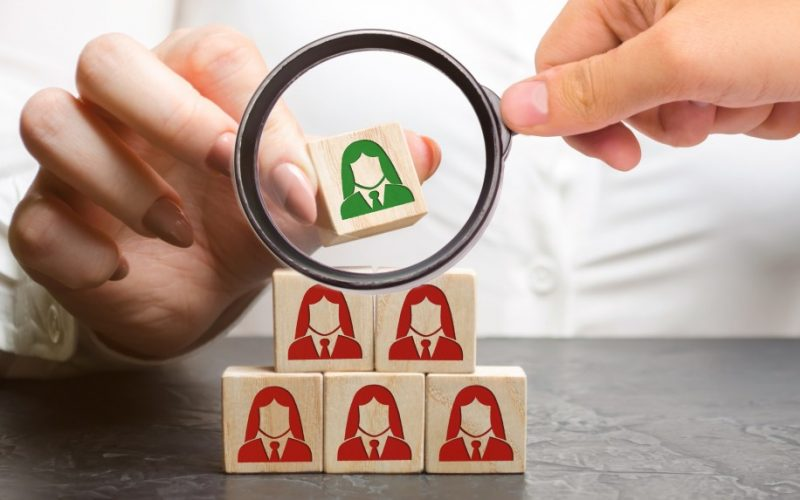 businesswoman-puts-wooden-blocks-with-the-image-of-female-employees-the-concept-of-management-in